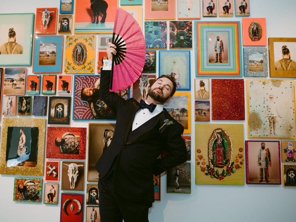 LGBTQ groom in a formal tux flourishes large fan in front of colorful collage exhibit in 21c Hotel Lexington