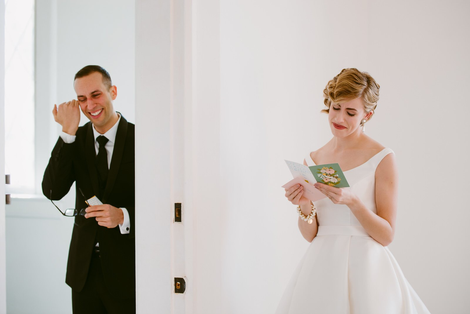 vintage-styled bride smiles holding groom's letter to her while groom holding her letter to him also cries and wipes eyes at Loudon House KY