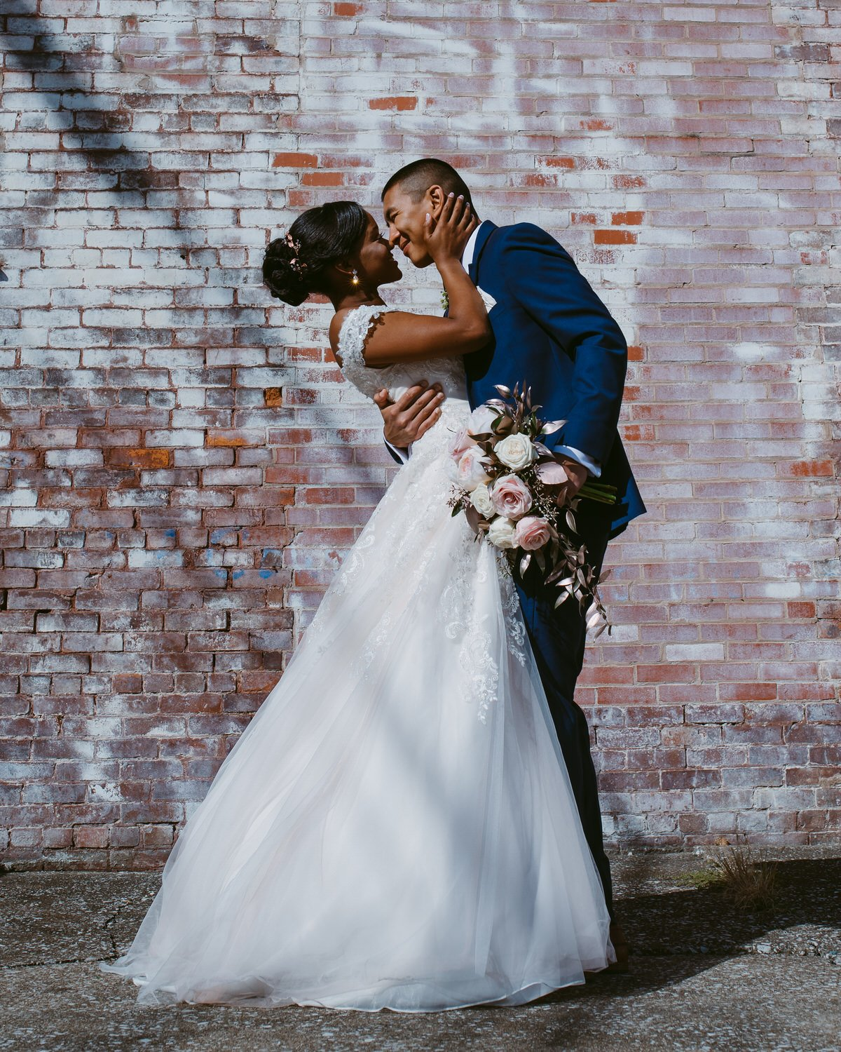groom holding wedding bouquet romantically dips bride against a brick city backdrop in Versailles Ky near The Galerie Venue