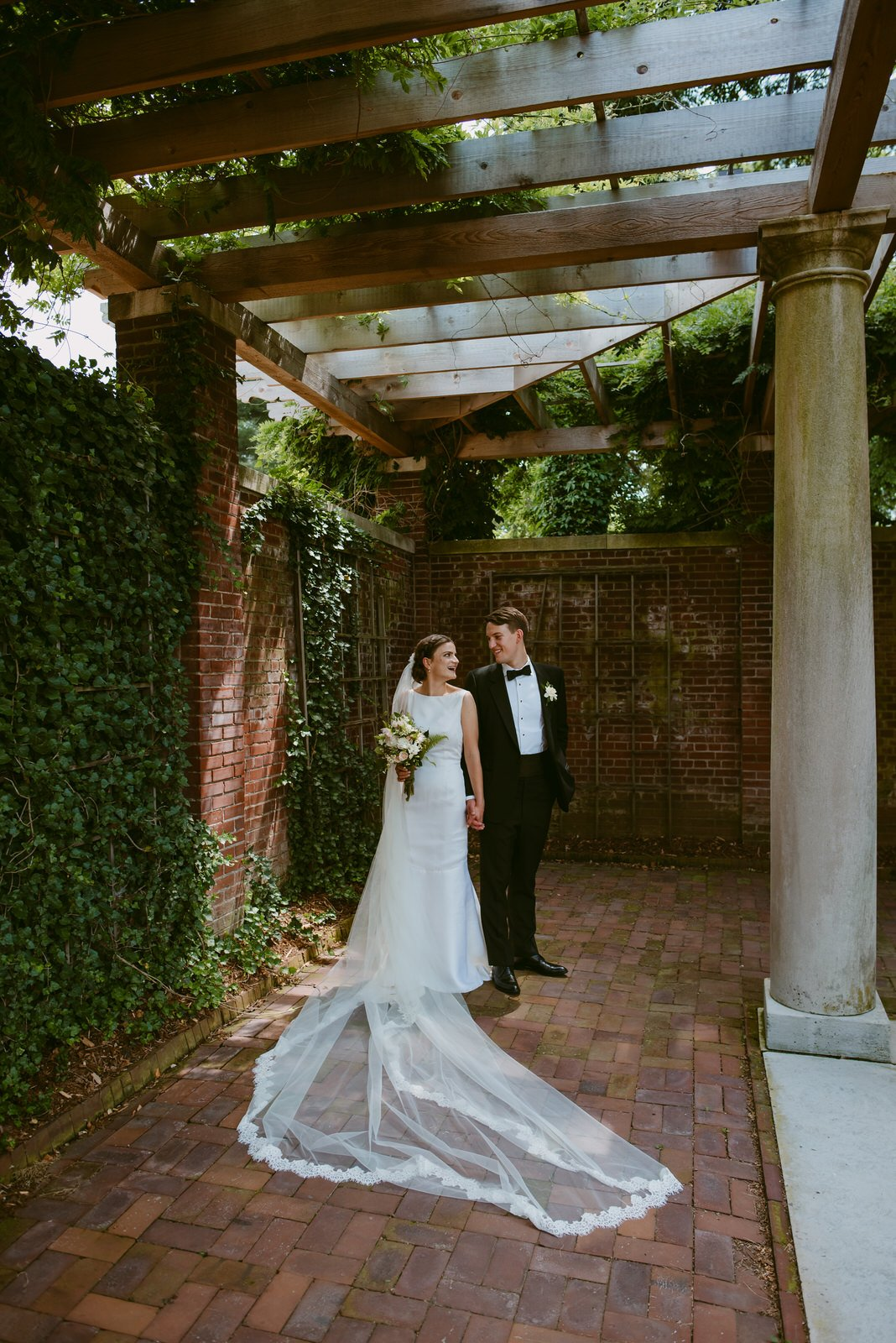 bride in classic dress with cathedral veil and groom in tux hold hands smile at each other beneath long tunnel arbor at Garden Court Venue