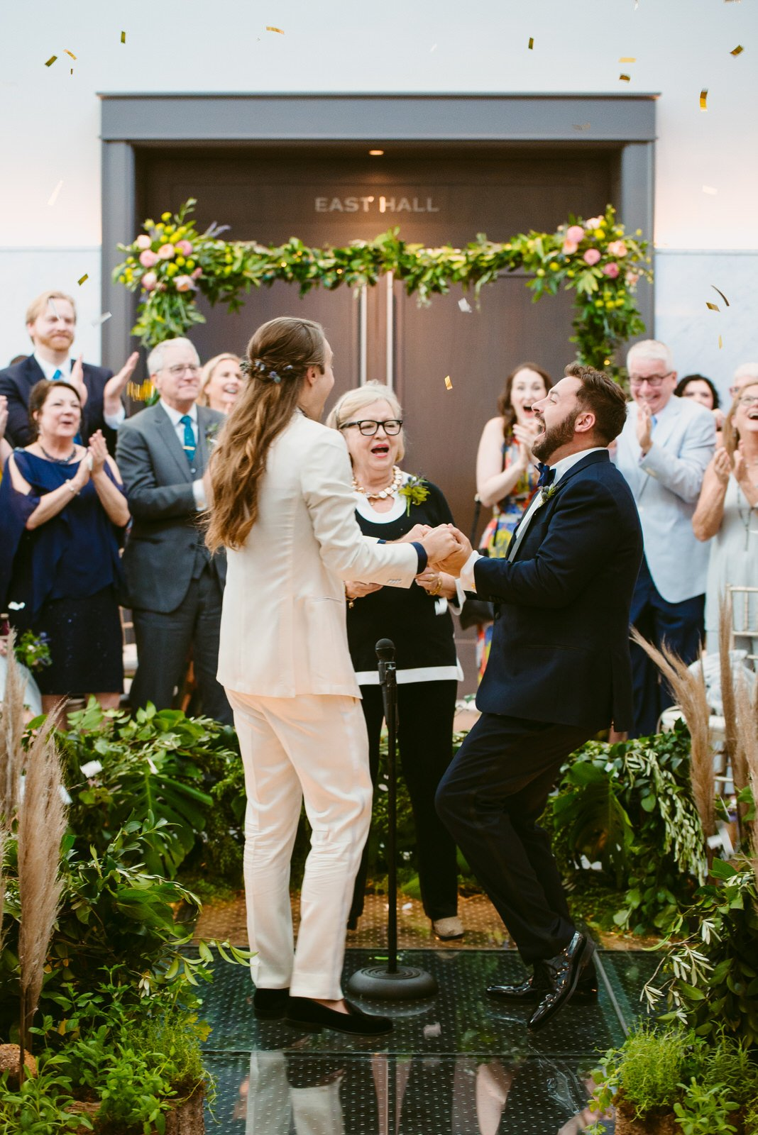 groom in white tux and groom in classic tux hold hands and celebrate amid clapping wedding guests and swirling confetti at Limestone Hall