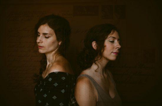 postcard script double exposure of two women back to back in low lit studio in Lexington Kentucky