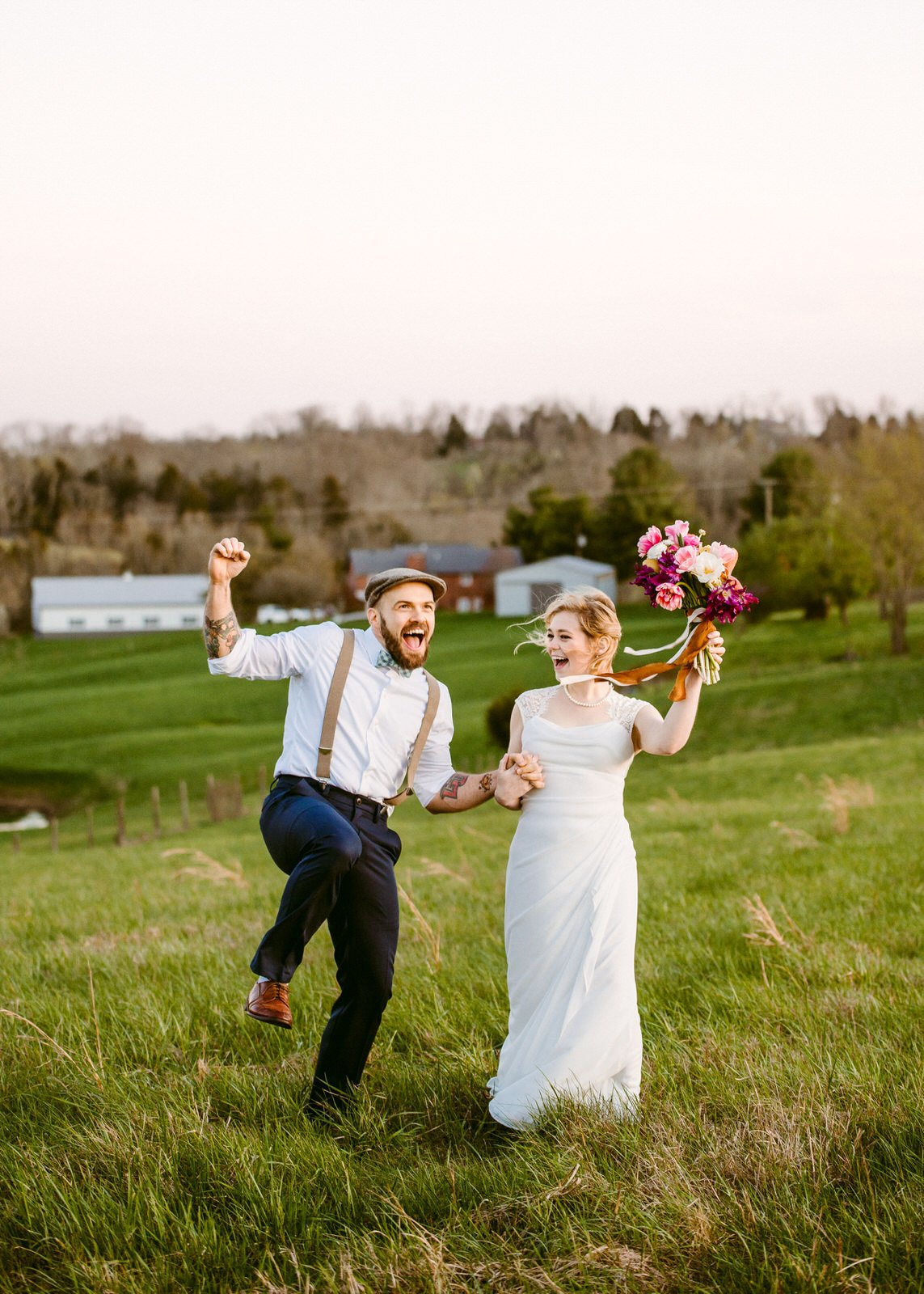 groom in suspenders and bride with bouquet on a hill celebrate and jump on a hillside overlooking a Kentucky farm