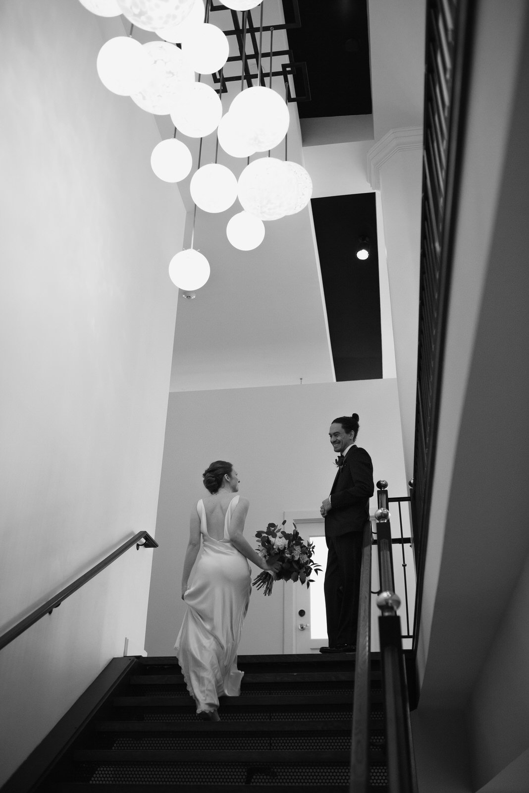 bride in A La Robe dress walks up modern Hotel Covington Staircase towards groom underneath glass art lighting installation