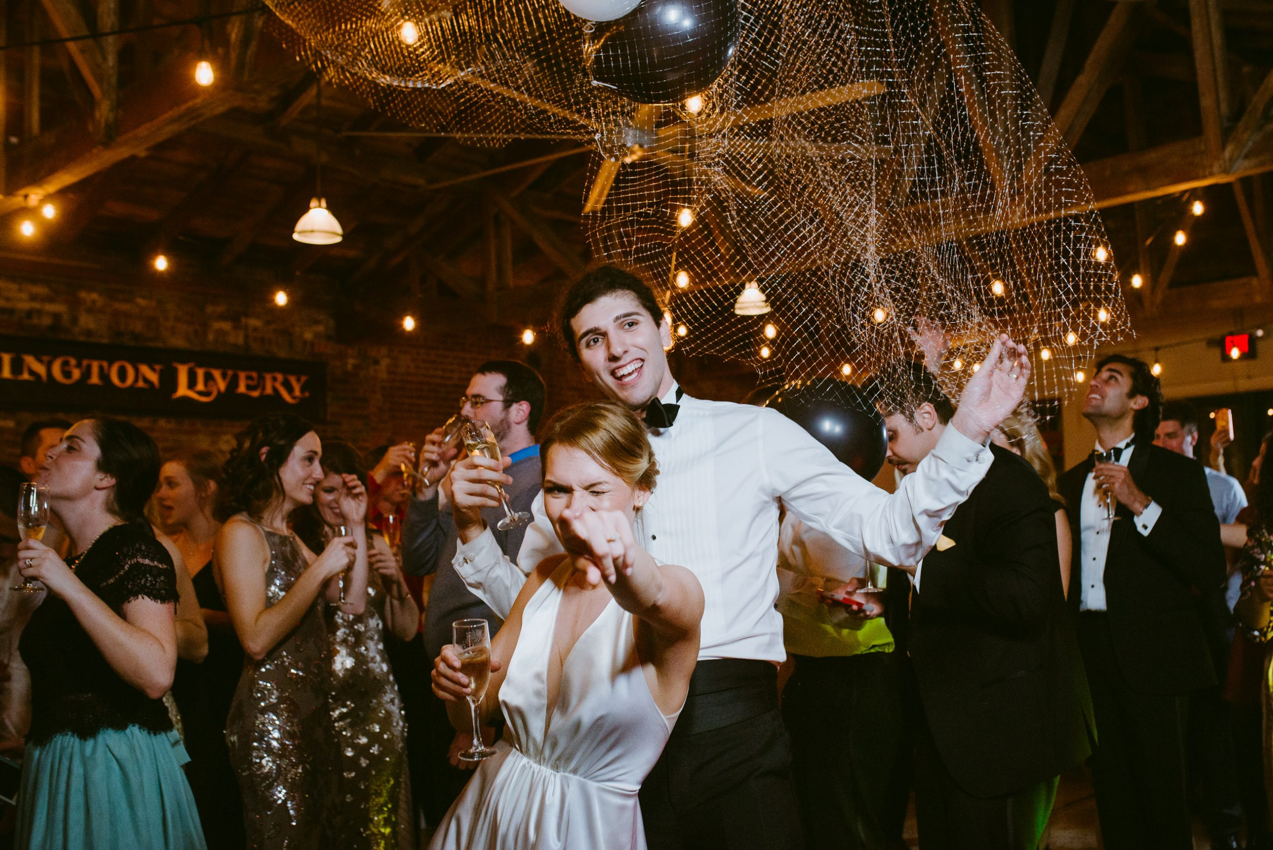 bride points at camera while groom in tux brandishes champagne just after New Years balloon drop at Lexington Livery Venue while guests celebrate behind
