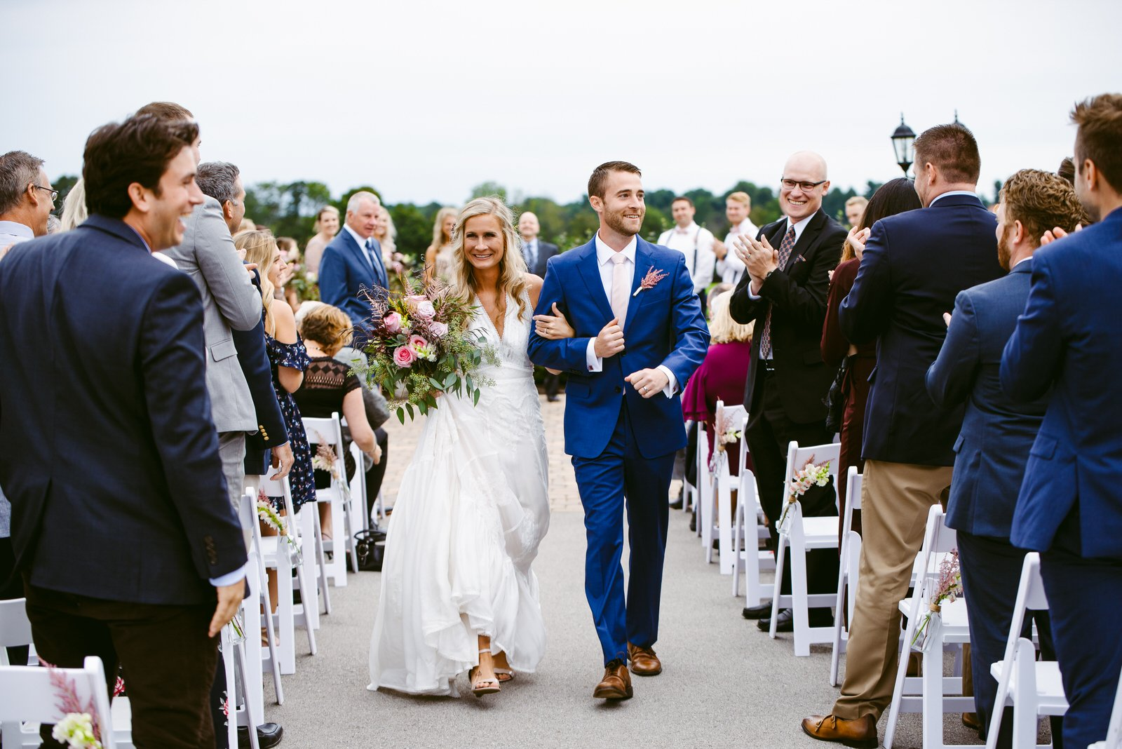 happy bride in boho dress and groom with blue suit stride down aisle at Thoroughbred Center Lexington while guests clap and smile