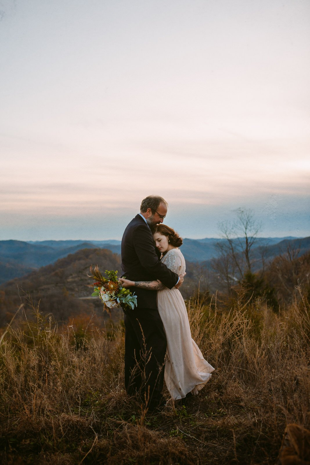 bride in embroidered dress and tattoos embraces groom in black suit standing on high hill with grasses and Kentucky mountains in background