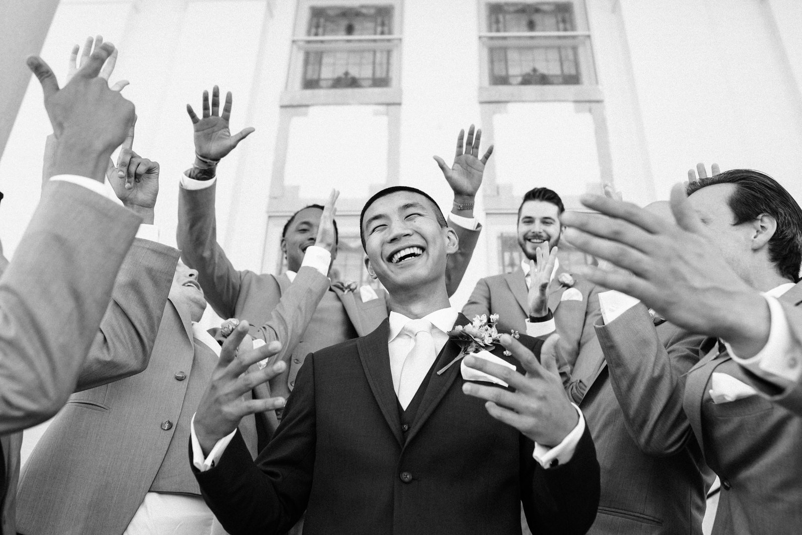 groom laughs and celebrates with group of groomsmen around him all raising their hands at The Galerie Venue Kentucky