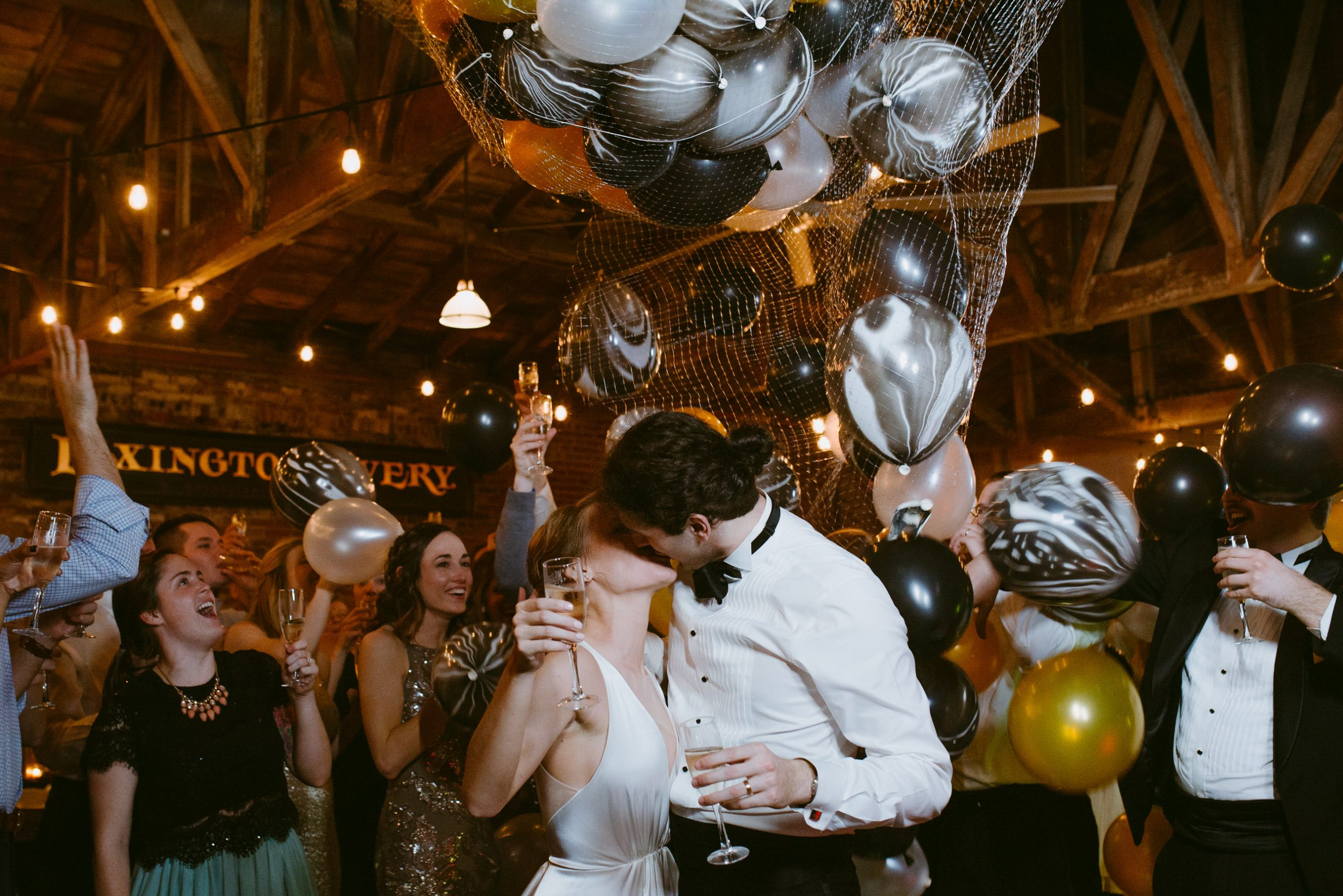 bride and groom kiss with champagne just after a new years balloon drop at Lexington Livery kentucky Venue while guests celebrate behind