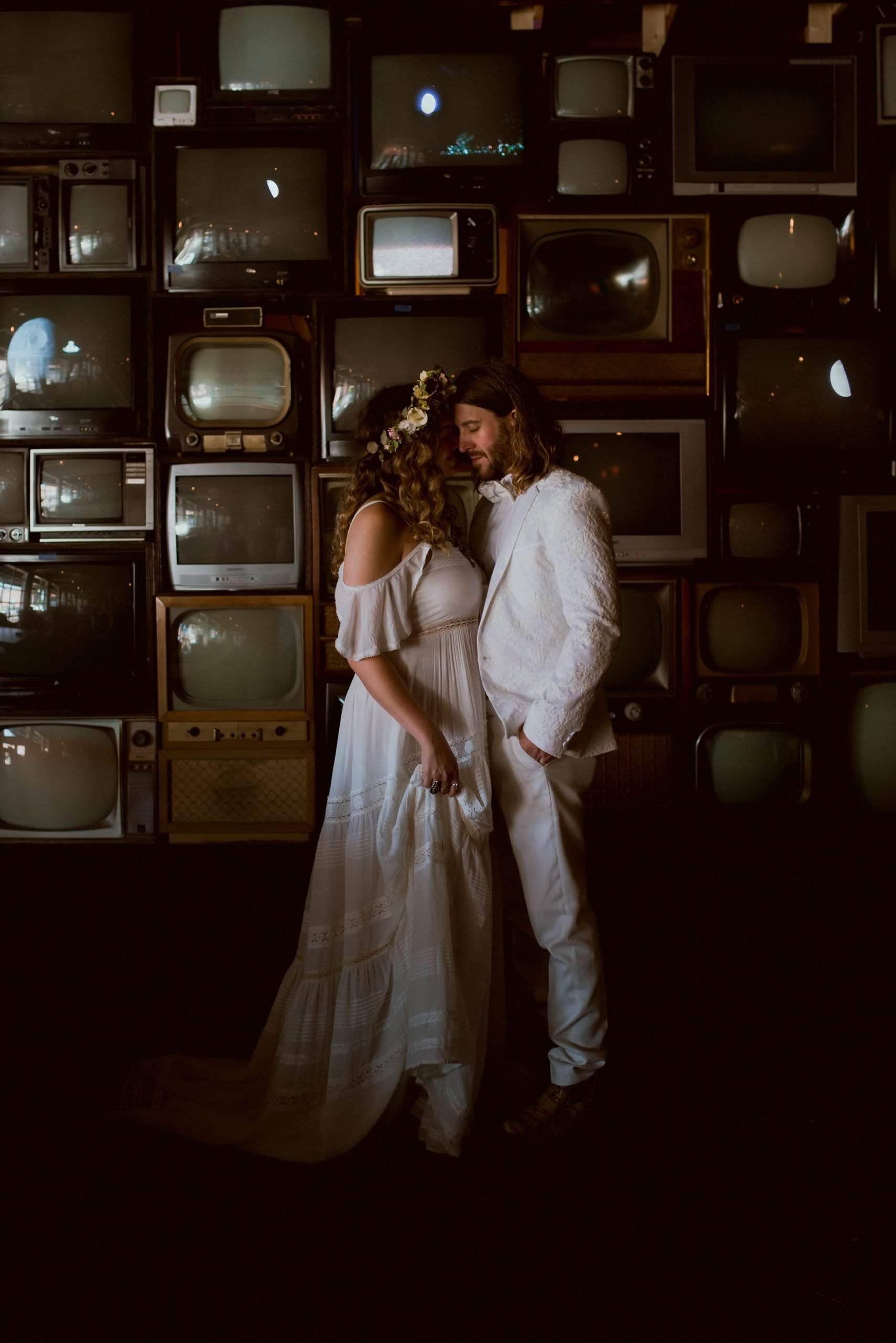 bride in boho wedding dress flower crown cuddles closely with groom in white tux snakeskin boots against wall of televisions at The Burl Venue Kentucky