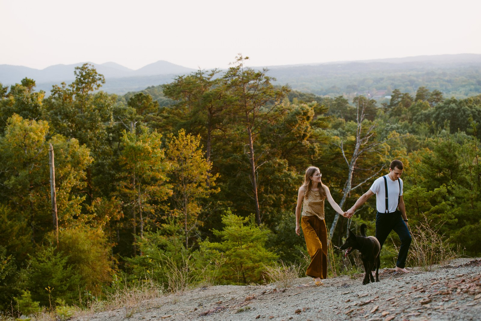 man and woman walking on a rocky hillside looking out across Red River Gorge landscape black dog walks ahead