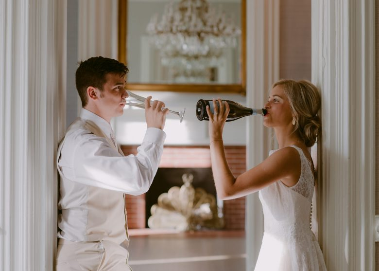 elopement couple leaning in doorway drink champagne together at griffin gate manor in Kentucky