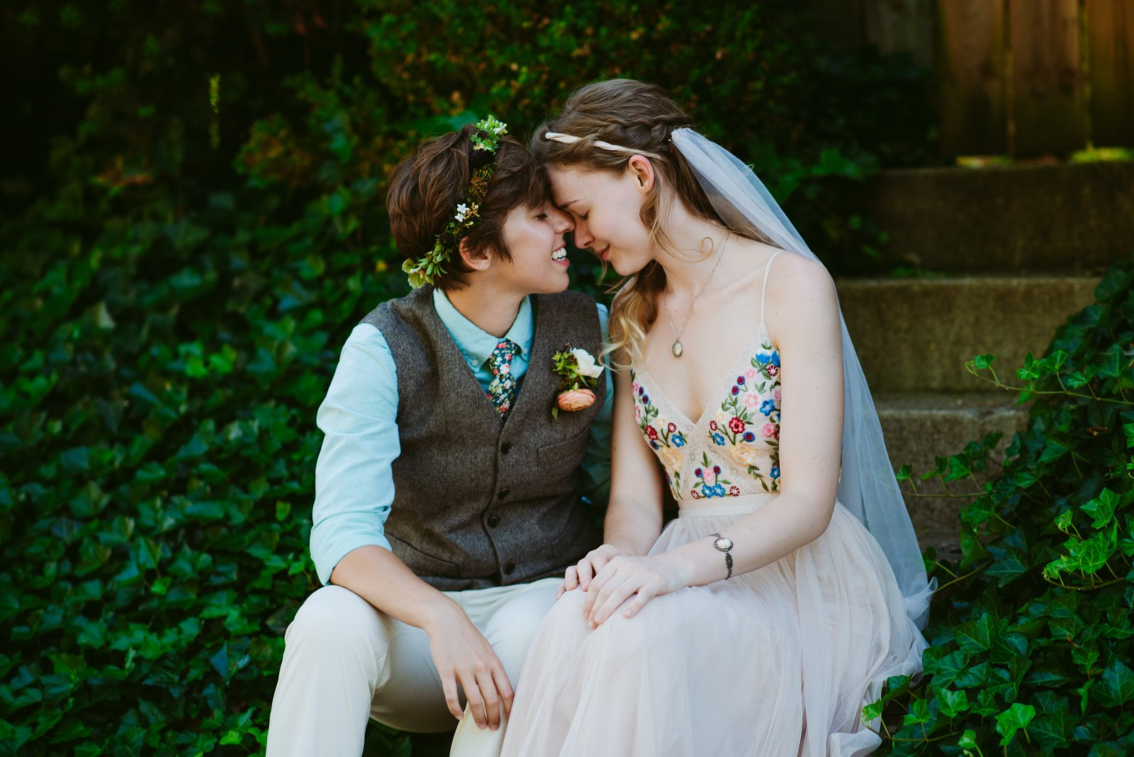 bride in suit and bride in BLDHN dress sitting on ivy covered steps touch foreheads and embrace before wedding