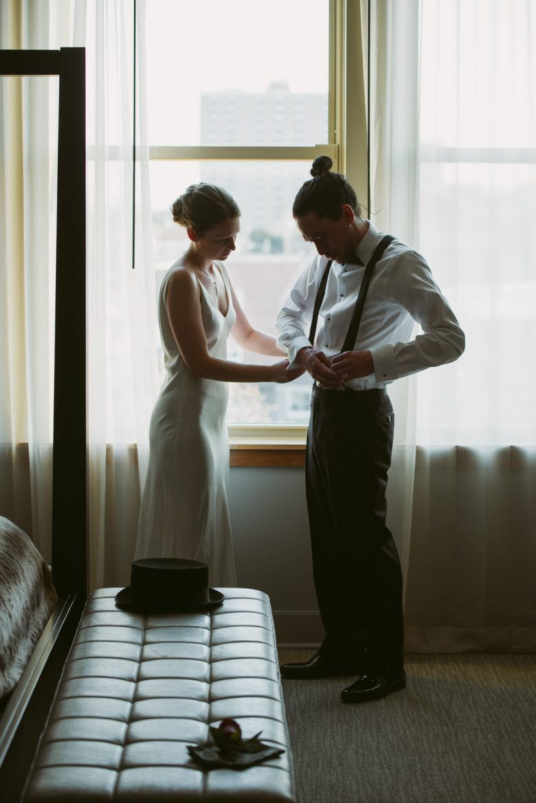 bride and groom help each other get ready at Hotel Covington