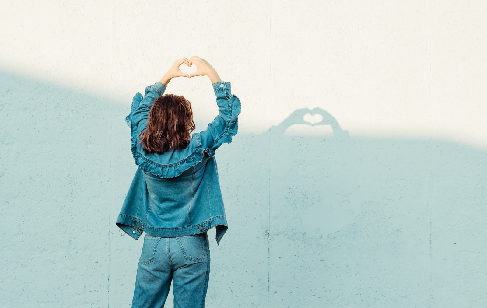 woman in jeans and jean jacket uses her hands to make a heart shaped shadow against shadowed white walls