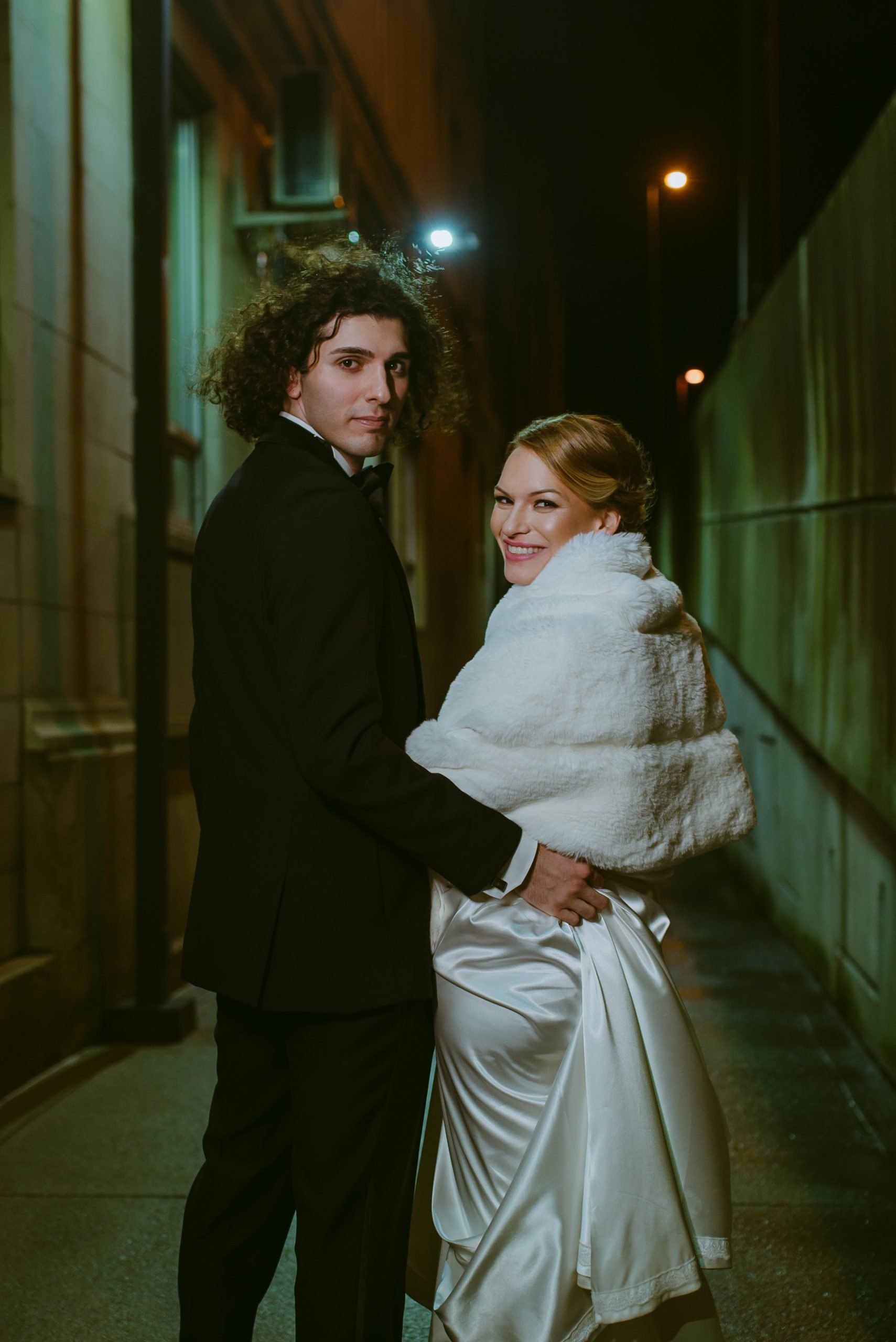 groom in tux and bride with white fur shawl look over shoulders while walking down city alley by Lexington Livery Lexington Kentucky